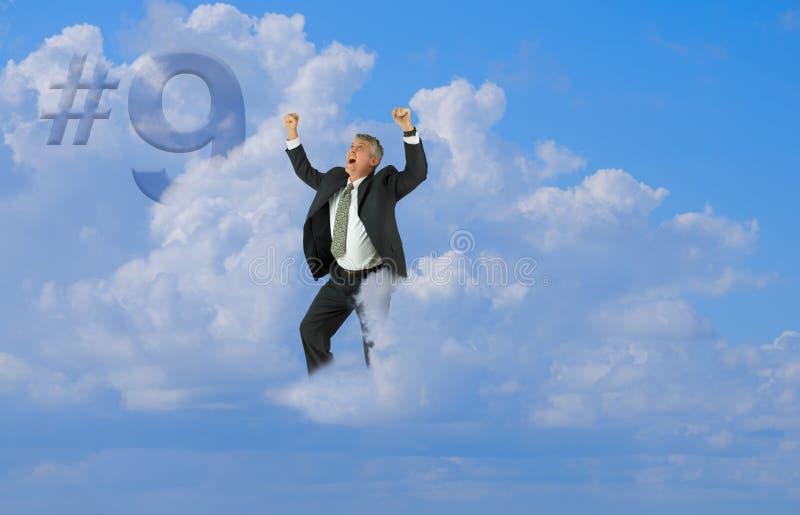 O homem feliz entusiasmou o sorriso com os braços que flutuam acima na nuvem nove imagem de stock