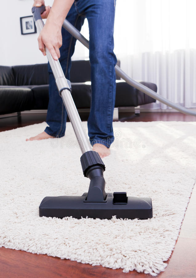 O homem feliz está limpando na sala moderna com o vácuo. fotos de stock royalty free