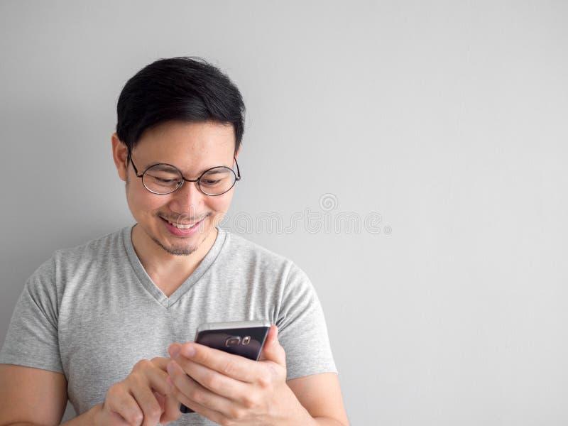O homem feliz está usando o smartphone Conceito de usar meios sociais sobre foto de stock royalty free