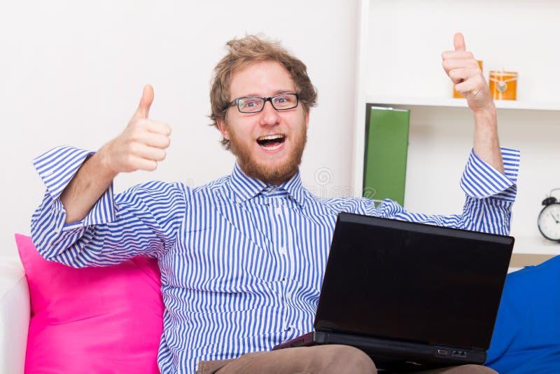 O homem feliz mostra o sinal APROVADO na frente de um computador fotos de stock