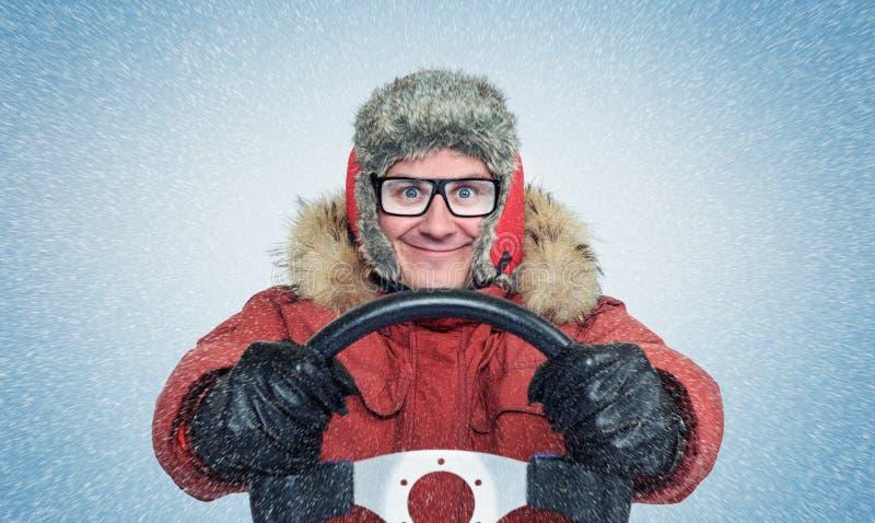 O homem feliz no inverno veste-se com um volante, blizzard da neve Motorista do conceito foto de stock