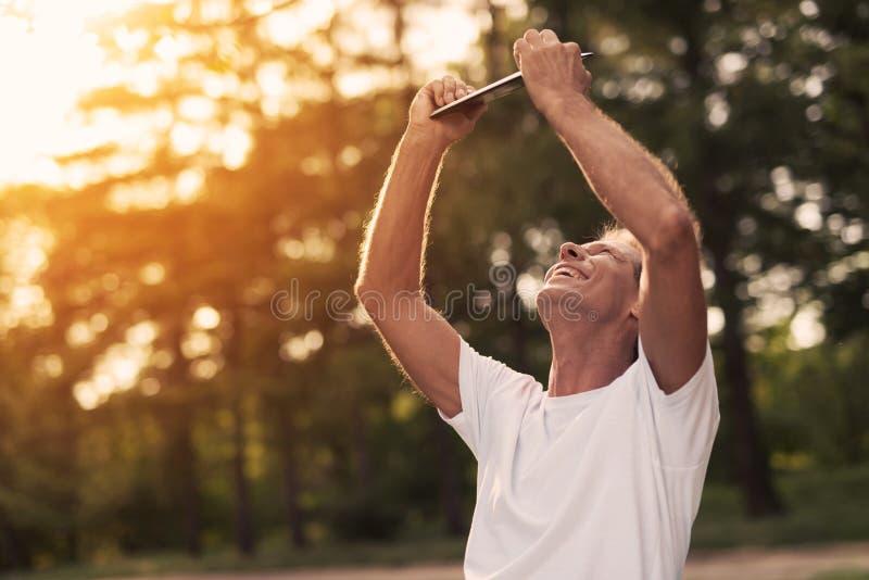 O homem feliz no parque levantou suas mãos acima e olha algo em sua tabuleta fotografia de stock