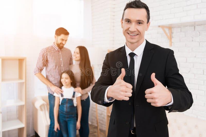 O homem feliz no terno mostra os polegares acima Casa para a venda A família nova olha apartamentos imagens de stock royalty free