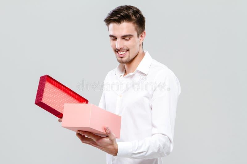 O homem feliz novo está abrindo uma caixa atual foto de stock royalty free