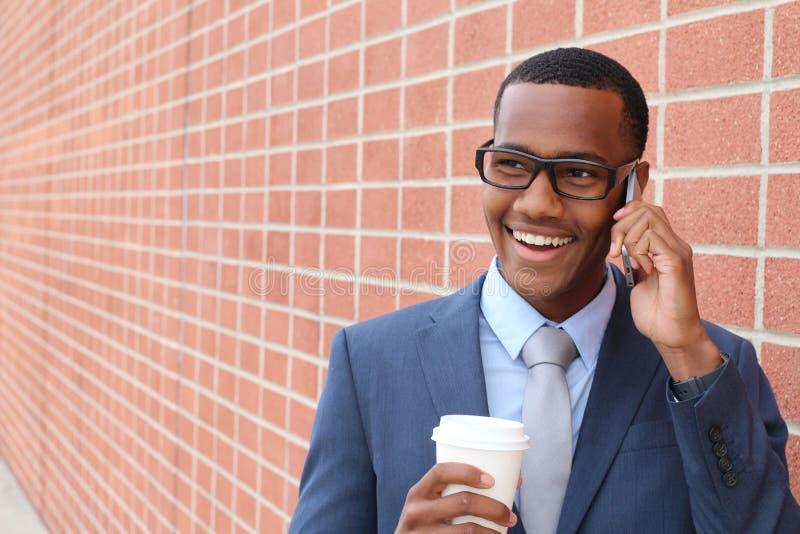 O homem feliz novo que fala no telefone celular isolou fora o fundo urbano da parede da cidade imagem de stock