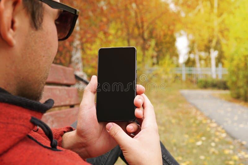 O homem feliz novo realiza em sua mão seu smartphone e mostra a tela Tecnologia e povos use o smartphone fora no aberto imagens de stock