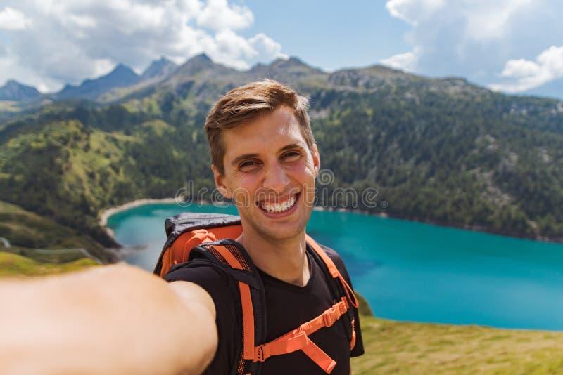 O homem feliz novo toma um selfie na parte superior da montanha nos cumes suíços fotos de stock