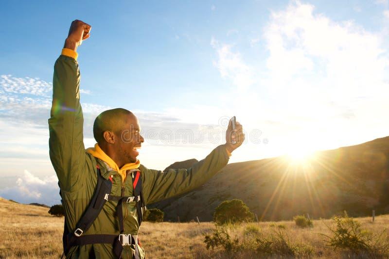 O homem feliz que caminha nas montanhas com braço aumentou ao tomar o selfie com telefone celular imagens de stock