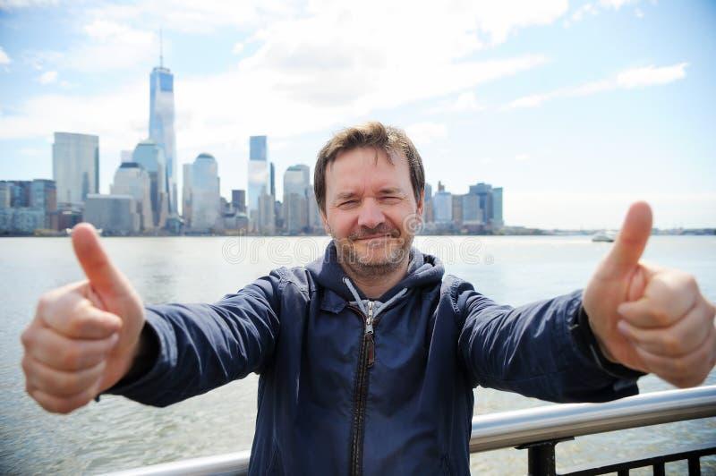 O homem feliz que dá os polegares levanta o sinal imagem de stock