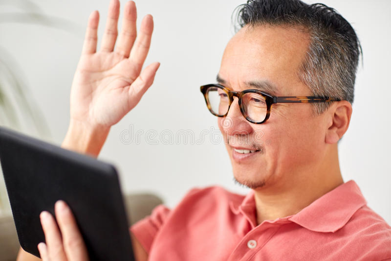 O homem feliz que tem o vídeo chama o PC da tabuleta em casa fotos de stock royalty free