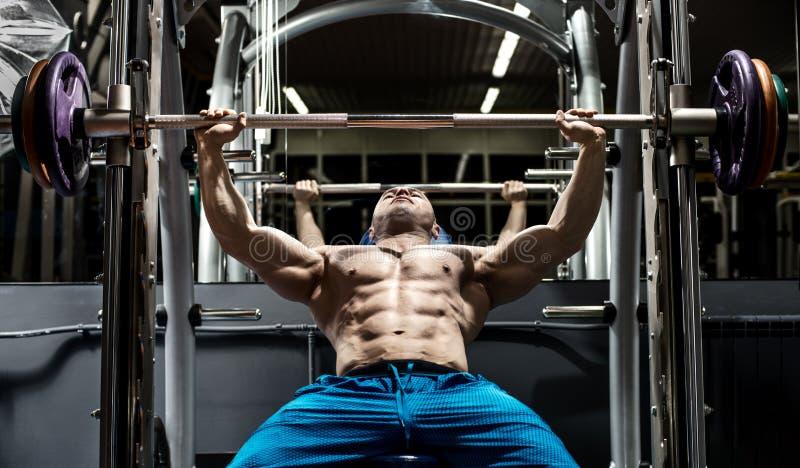 O homem fisiculturista faz exercício foto de stock royalty free