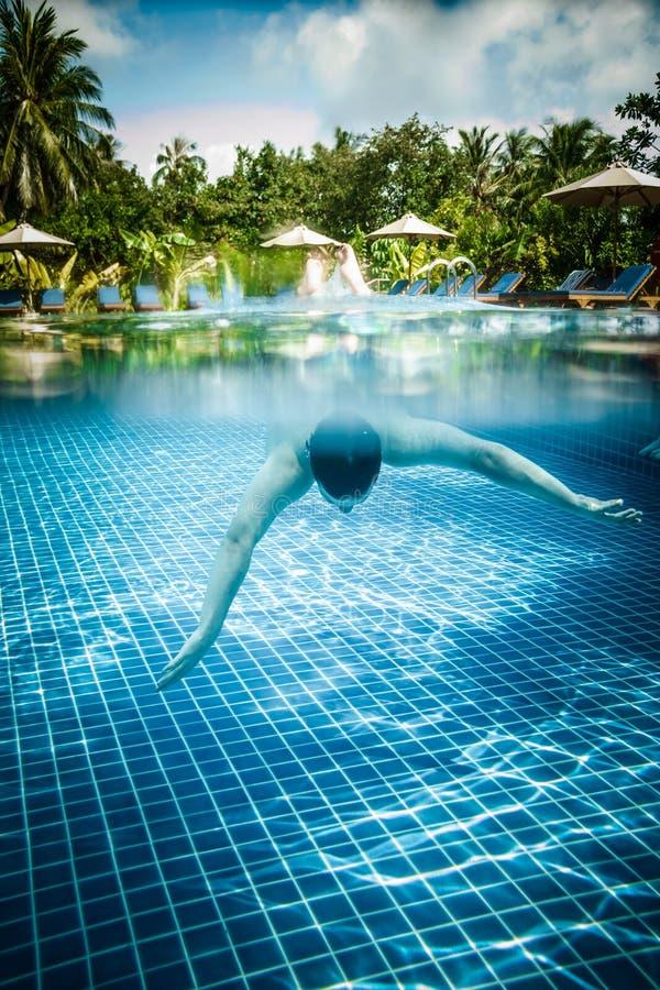 O homem flutua debaixo d'água na associação foto de stock