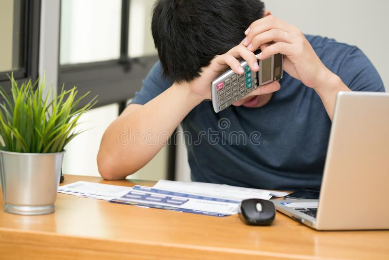 O homem forçaram o quando calculam o débito do cartão de crédito com uma calculadora e o trabalho no portátil em casa, triste asi imagem de stock royalty free