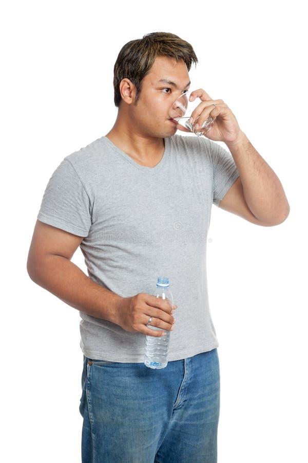 O homem forte asiático é água potável de um vidro fotografia de stock royalty free