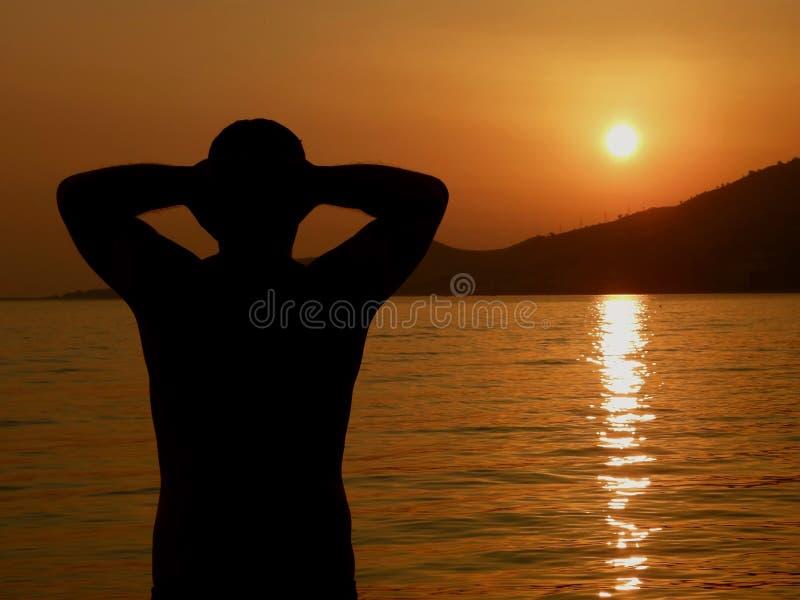 O homem forte, atrativo relaxa no por do sol no mar fotografia de stock