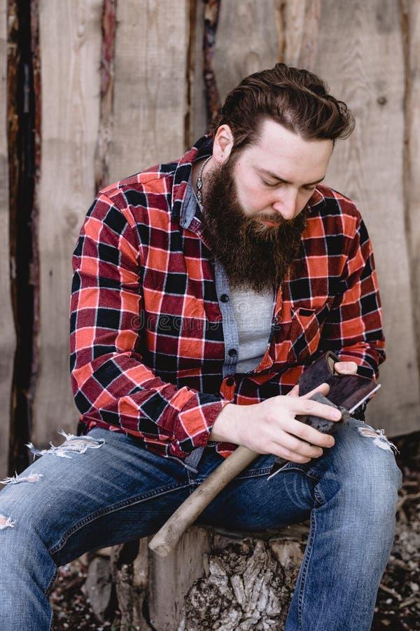 O homem forte brutal com uma barba vestida em uma camisa verificada e em umas calças de brim rasgadas está sentando-se com um mac fotos de stock royalty free