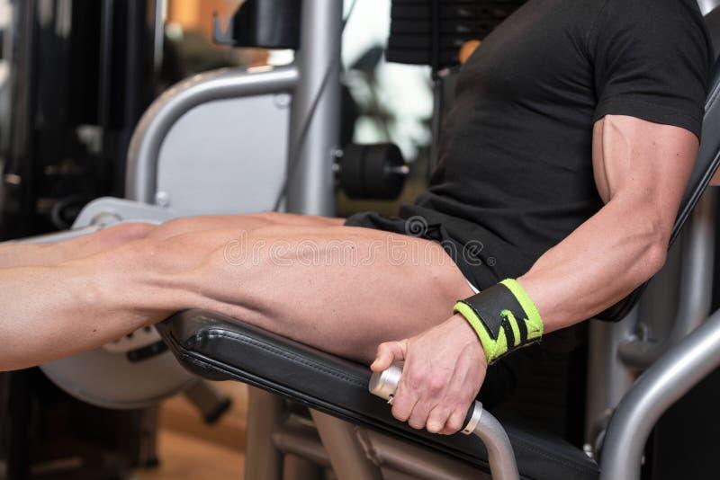 O homem forte considerável executou o exercício da imprensa do pé no gym foto de stock