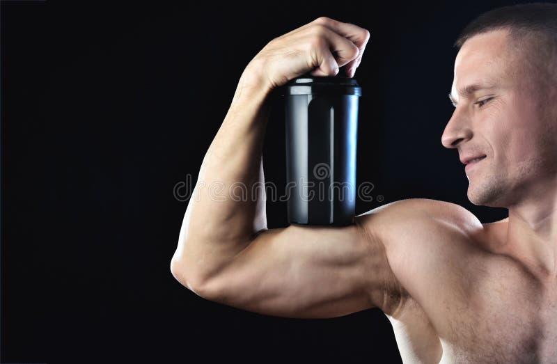 O homem forte do músculo guarda em um bíceps um abanador preto com proteína imagem de stock royalty free