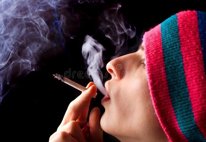 O homem fuma imagem de stock