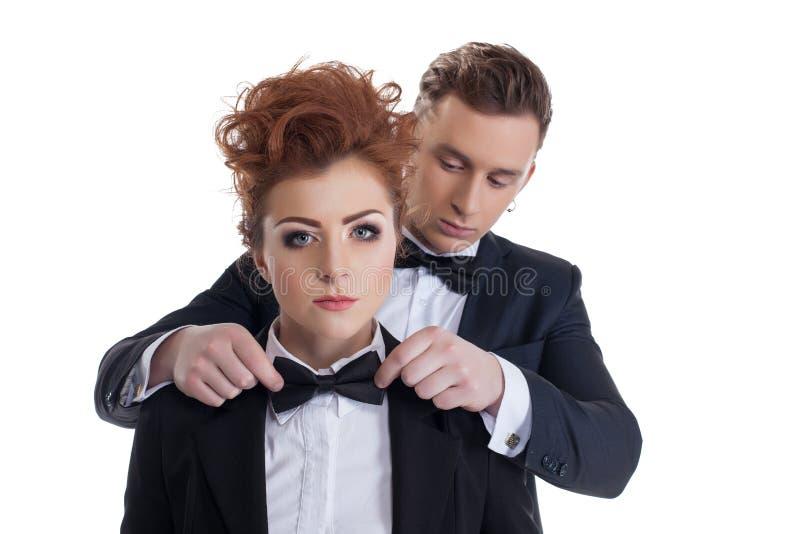 O homem galhardo endireita o laço a sua amiga 'sexy' fotografia de stock royalty free
