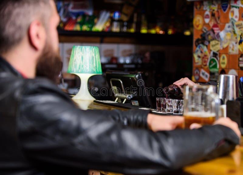 O homem gasta o lazer no bar escuro O homem senta-se no contador da barra no bar Estilo de vida do fim de semana Álcool de derram fotos de stock royalty free