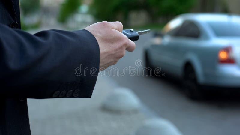 O homem gerencie sobre o alarme do carro, conceito da segurança, risco de carro do desvio de avião estacionado na rua foto de stock royalty free