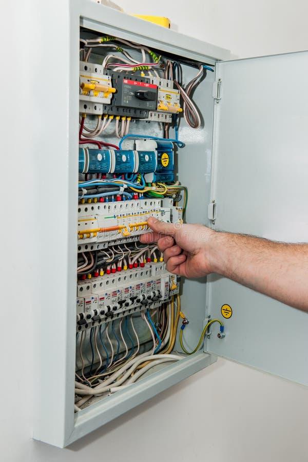 O homem gerencie sobre o interruptor elétrico sobre o painel de distribuição elétrica Verificando o equipamento elétrico no novo foto de stock royalty free