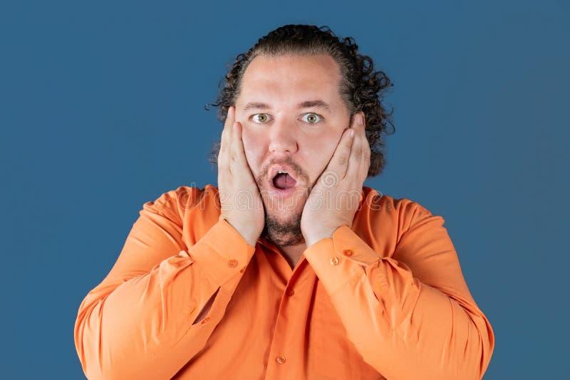 O homem gordo na camisa alaranjada guarda suas mãos sobre sua cara É surpreendido muito imagens de stock