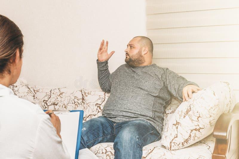 O homem gordo no esforço diz emocionalmente sobre seus depressão e problemas Consulta do psicólogo fotografia de stock