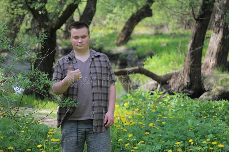 O homem gordo novo está com o o seu de volta ao rio Aumentou acima o polegar As mostras gostam No parque entre a folha verde-clar imagens de stock royalty free