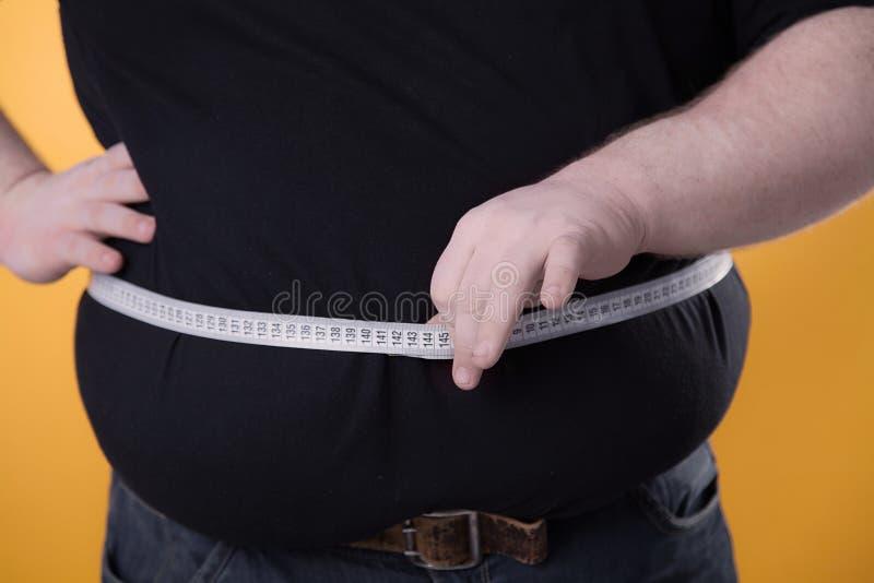 O homem grande faz medidas com a fita de seu estômago gordo fotografia de stock royalty free