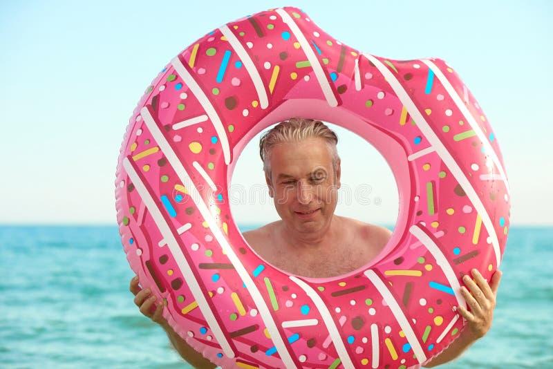 O homem grisalho nada em um círculo inflável no mar imagem de stock