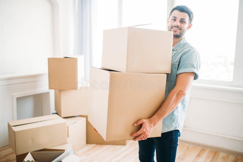 O homem guarda caixas nas mãos, transportando-se à casa nova fotografia de stock