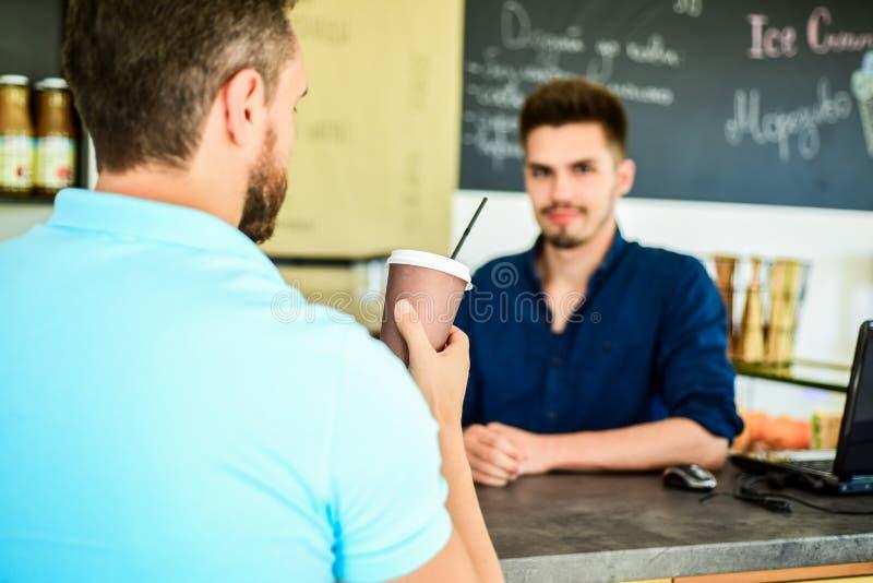 O homem guarda o copo de papel com suporte do indivíduo do barista do café no fundo O cliente obteve sua bebida Tenha o sorvo da  fotografia de stock