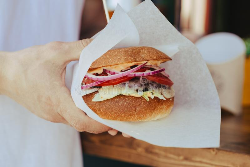 O homem guarda o hamburguer com m?os no fundo no caf? fotos de stock royalty free