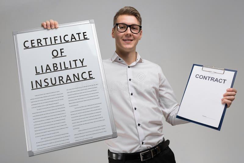 O homem guarda um cartaz com o certificado da inscrição do seguro de responsabilidade e um certificado vazio isolado fotos de stock royalty free