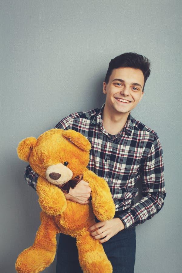 O homem guarda o urso de peluche em uma luz - fundo azul, espaço da cópia Conceito bonito do brinquedo Urso bonito do brinquedo d foto de stock