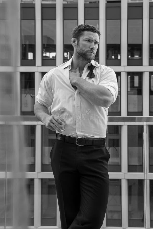 O homem hunky considerável com camisa desabotoada e bowtie fraco está no balcão do hotel com contexto do sckyscraper imagens de stock royalty free