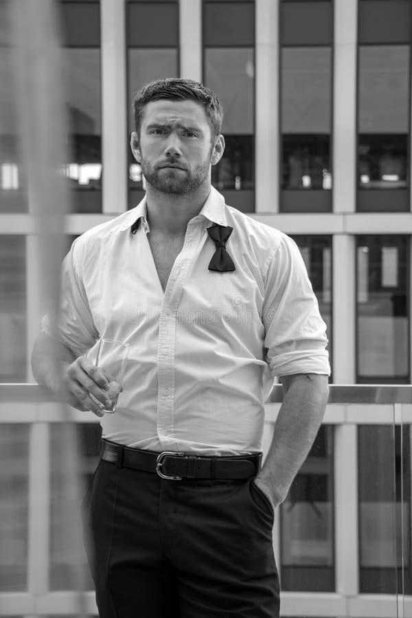 O homem hunky considerável com camisa desabotoada e bowtie fraco está no balcão do hotel com contexto do sckyscraper foto de stock