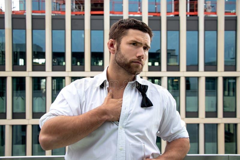 O homem hunky considerável no smoking, na camisa desabotoada e no laço está no balcão do hotel, bebendo uma bebida foto de stock