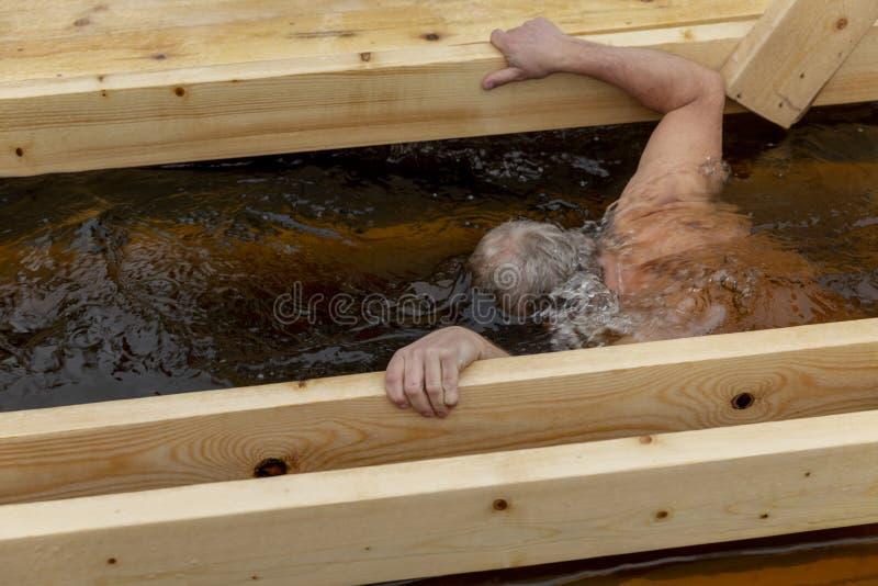 O homem idoso banha-se no furo do gelo no inverno fotos de stock