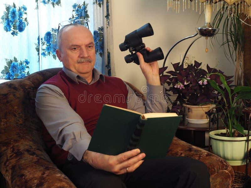O homem idoso com binóculos em uma cadeira foto de stock royalty free