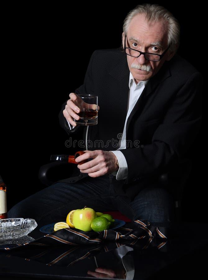 O homem idoso com um vidro do uísque no preto foto de stock royalty free