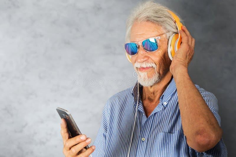 O homem idoso escuta música com fones de ouvido fotografia de stock royalty free