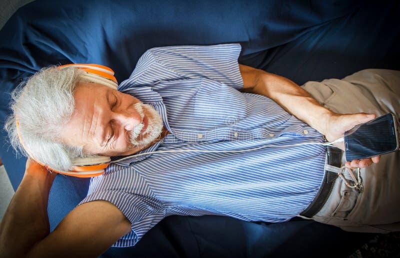 O homem idoso escuta música com o fones de ouvido no sofá fotos de stock royalty free