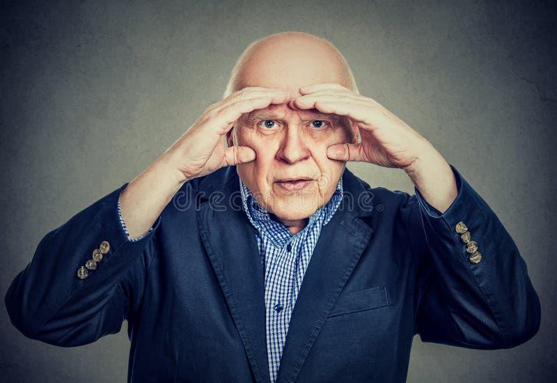 O homem idoso irritado que olha através das mãos como binóculos tem problemas da visão fotografia de stock royalty free
