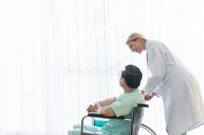 O homem idoso paciente está sentando-se em uma cadeira de rodas com posição do fisioterapeuta atrás de feliz e do sorriso fotografia de stock royalty free