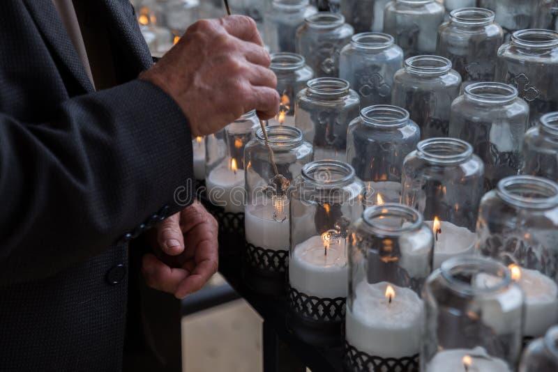 O homem ilumina velas em uma igreja Católica foto de stock royalty free