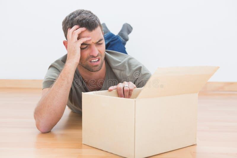 O homem incomodado abre uma caixa movente em casa fotos de stock