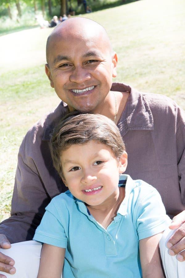 O homem indiano ou mexicano senta-se na grama com a criança misturada do menino do filho imagens de stock royalty free